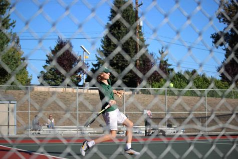 A Shorecrest tennis player aims to hit the ball in the midst of competition.
