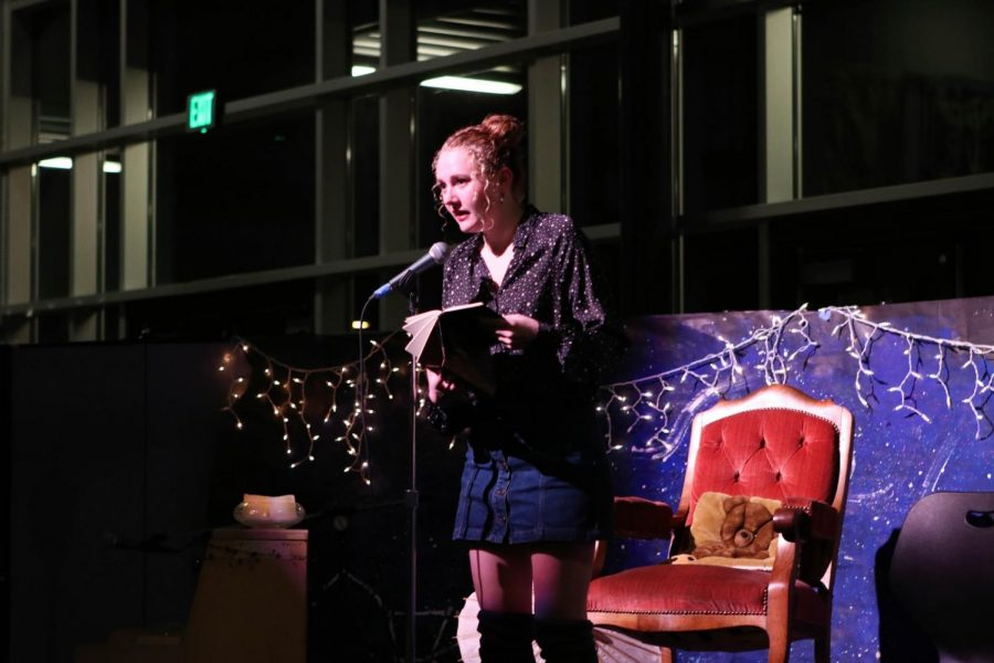 Editor Haley Larson stands reading one of her poems at the microphone of Tattoo's Coffeehouse.