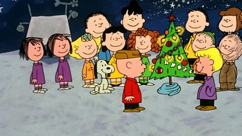 Charlie Brown and friends sing around the Christmas tree.